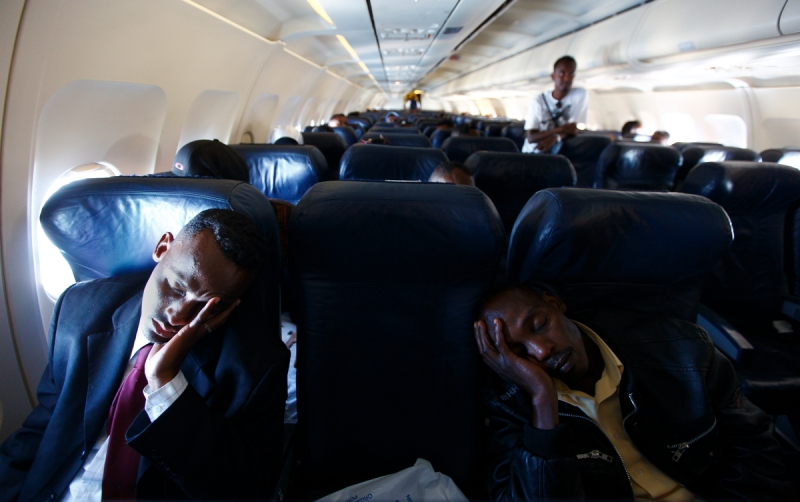 Refugees sleep on a plane heading to Paris from Malta July 5, 2010. A group of 93 African and Iraqi refugees were relocated to France on Monday as part of the intra-EU Relocation from Malta (EUREMA) pilot project, which aims to relocate refugees from Malta to other EU member states. .