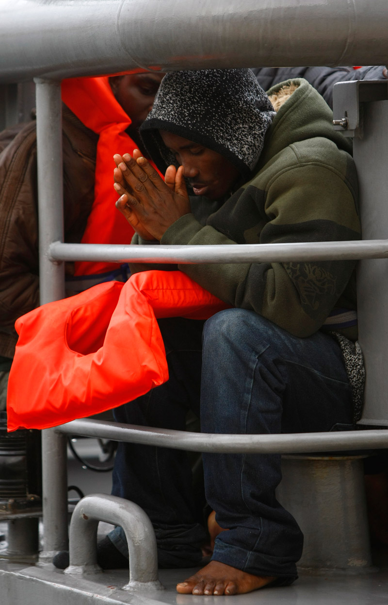 A would-be immigrant prays while sitting on the deck of an Armed Forces of Malta (AFM) patrol boat as it arrives at the AFM Maritime Squadron base at Haywharf in Valletta's Marsamxett Harbour December 29, 2008. Some 140 African would-be immigrants, believed to be from Somalia, Ghana and Nigeria, were rescued by the AFM 87 nautical miles south-south-west of Malta when they found themselves in difficulty while on their way to reach European soil from Africa, authorities said
