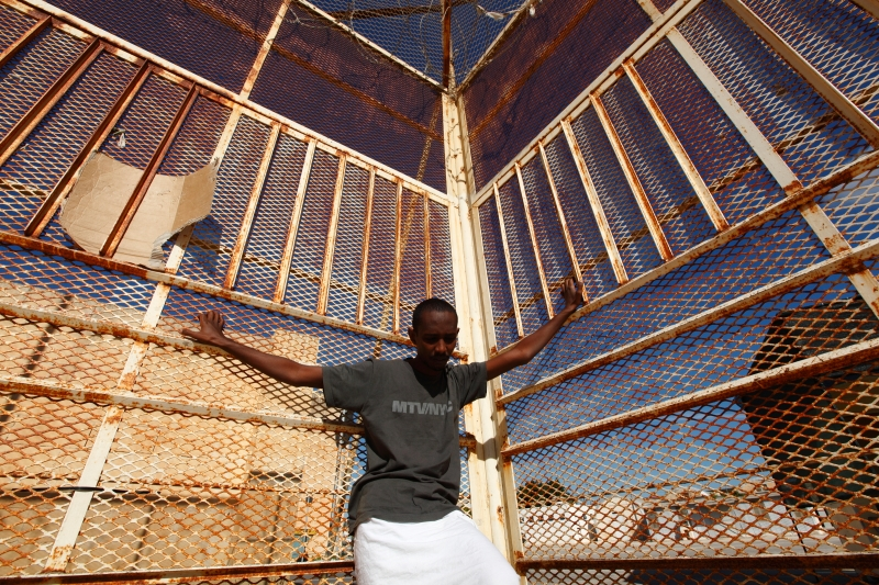 A 29-year-old Eritrean migrant stands against a fence at the Safi barracks detention centre for immigrants in Safi, outside Valletta, October 22, 2013.