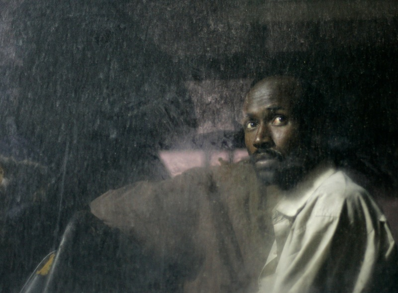 A Somali man looks out of the window of a police bus after arriving in the fishing village of Marsaxlokk, in the southeast of Malta, May 26, 2007. Twenty-nine Somali asylum seekers were intercepted aboard a makeshift boat seven miles south-west of the Maltese islands on their way to reach European soil from Africa.