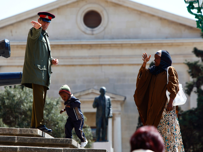 An AFM soldier gives directions to a Somali refugee woman in front of the Office of the Prime Minister at Castille Place in Valletta.