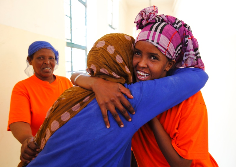A newly-arrived Somali migrant is greeted by an old friend at the Lyster barracks detention centre for immigrants in Hal Far, outside Valletta, July 10, 2013.  The two women said they had been held in detention together in Libya for seven months.  Migrants who land in Malta face mandatory detention that can last for 18 months but figures show nearly half are allowed out sooner, following the granting of refugee status or humanitarian protection, according to official sources.