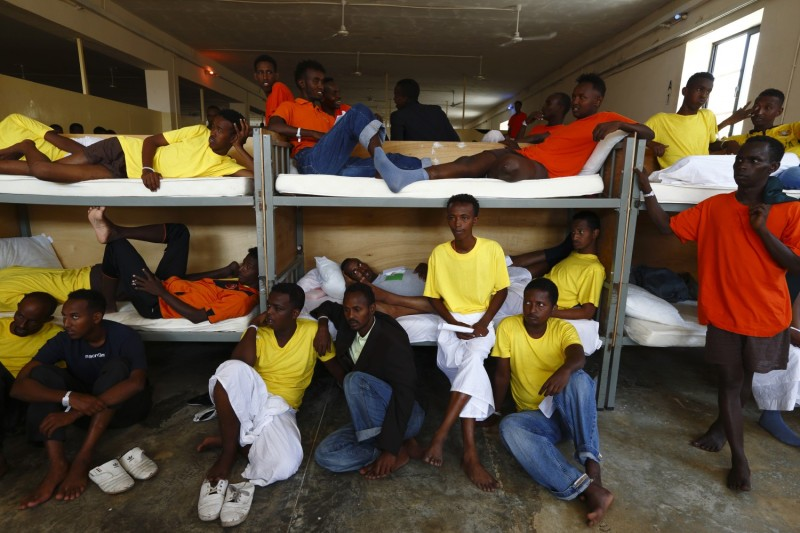 Immigrants sit in their dormitory at the Safi barracks detention centre for immigrants that currently holds around 600 detainees in Safi, outside Valletta, July 19, 2013. Migrants who land in Malta face mandatory detention that can last for 18 months but figures show nearly half are allowed out sooner, following the granting of refugee status or humanitarian protection, according to official sources.  Malta will be given concrete assistance by the European Commission to return failed asylum seekers to their country of origin, the government has announced.