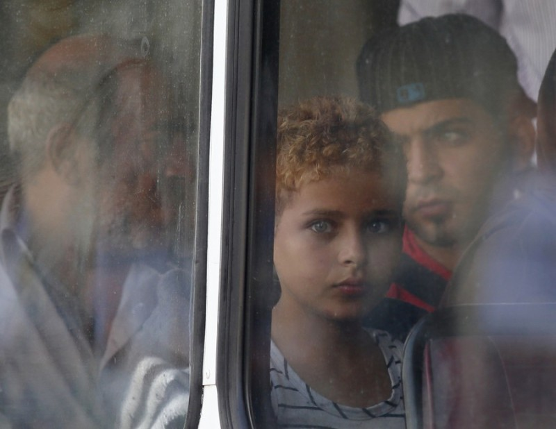 A rescued migrant child looks out of the window of a police bus after arriving at the Armed Forces of Malta Maritime Squadron base at Haywharf in Valletta's Marsamxett Harbour October 12, 2013. Dozens of people died on Friday when a boat carrying around 250 migrants capsized between Sicily and Tunisia, in the second such shipwreck this month, the Italian coastguard said. 147 survivors, believed to all be Syrians, arrived in Malta on Saturday morning, according to local media.  REUTERS/Darrin Zammit Lupi (MALTA -