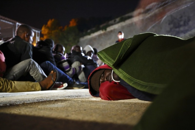 An ill irregular immigrant lies on the ground as a blanket is placed over him at the Armed Forces of Malta (AFM) Maritime Squadron base at Haywharf in Valletta's Marsamxett Harbour, early June 8, 2014.  129 Sub-Saharan African migrants were rescued by the AFM south of the Maltese islands when their boat ran into difficulties, according to army sources.