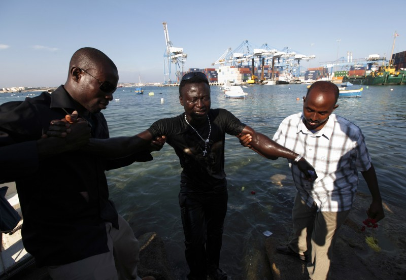 An African immigrant whose wife had drowned is helped out of the water after laying flowers in the sea, during a memorial service to commemorate those who died while crossing from Africa to Europe over the years, in Birzebbuga, outside Valletta, June 18, 2009.