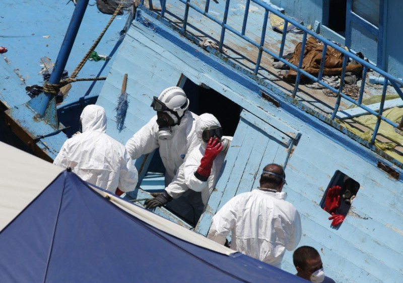Hazmat and forensic officers work on board a fishing boat, on which 19 migrants are reported to have died, at the Armed Forces of Malta (AFM) Maritime Squadron base in Valletta's Marsamxett Harbour, after it was towed to Malta by the AFM, July 20, 2014. Nineteen people died trying to reach Italy on a boat packed with hundreds of migrants, probably poisoned by carbon monoxide fumes from its engines, said the Italian Navy on Saturday, which has rescued more than 4,000 migrants in the last three days.