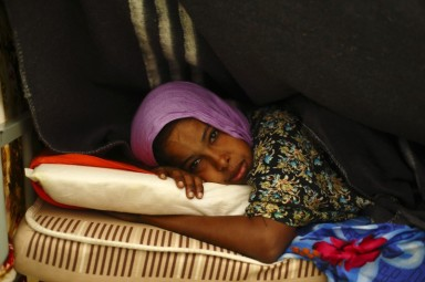 A Somali woman lies on her bed in a dormitory at the Lyster barracks detention centre for immigrants, which currently holds 236 detainees, in Hal Far, outside Valletta, October 22, 2013.