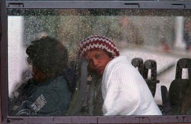 "A refugee from Sierra Leone, exhausted and lucky to be alive, slumps her head against the head rest on a Maltese Army coach near the Russian survey ship ""Akademia Nikolas Strakov"" in Grand Harbour in Valletta on December 6, 1998. The group of 52 refugees was rescued by the ship's crew 94 miles south-west of Malta. The 43 men and 9 women, from Sierra Leone, Egypt and Algeria, were found on a small open boat in rough seas. Eight of their colleagues are missing, believed drowned and a search for them was abandoned at sundown. They are believed to have been on their way to Italy."