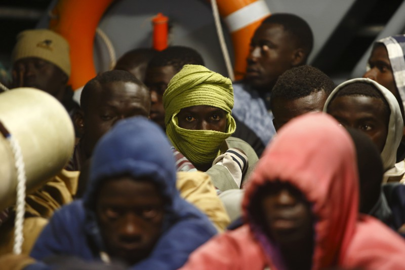 Immigrants sit on the deck of an Armed Forces of Malta (AFM) inshore patrol vessel after arriving at the AFM Maritime Squadron base at Haywharf in Valletta's Marsamxett Harbour, early June 8, 2014. A group of 130 Sub-Saharan African migrants were rescued by the AFM south of the Maltese islands when their boat ran into difficulties, according to army sources.