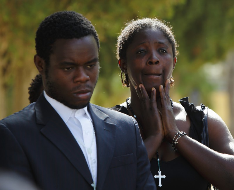 A Nigerian woman, whose husband drowned while attempting to reach Europe by sea, reacts as the coffin is lowered into a grave at Addolorata cemetery outside Valletta October 16, 2012.  Four Nigerian immigrants who lost their lives while attempting to reach Europe by sea were buried once DNA test results confirmed their identities.  The body of her husband was never found.