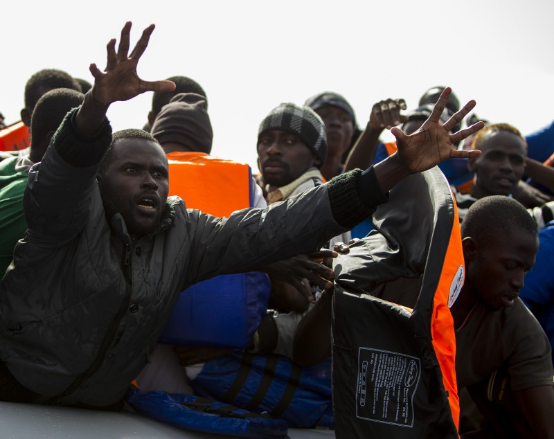 A group of 104 sub-Saharan Africans on board a rubber dinghy reach out for life jackets tossed to them by rescuers of the NGO Migrant Offshore Aid Station (MOAS) some 25 miles off the Libyan coast October 4, 2014. MOAS, a privately-funded humanitarian initiative, began operating at the end of August and has assisted in the rescue of some 2,500 migrants crossing from Libyan shores towards Europe.