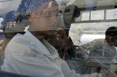 Asylum seekers sit in a police bus after disembarking from an Armed Forces of Malta (AFM) patrol boat, reflected in the bus window, at the AFM Maritime Squadron base at Haywharf in Valletta's Marsamxett Harbour July 26, 2007. The Armed Forces of Malta rescued twenty-nine asylum seekers when their makeshift boat started taking on water 60 nautical miles south of Malta while on their way to reach European soil from Africa.