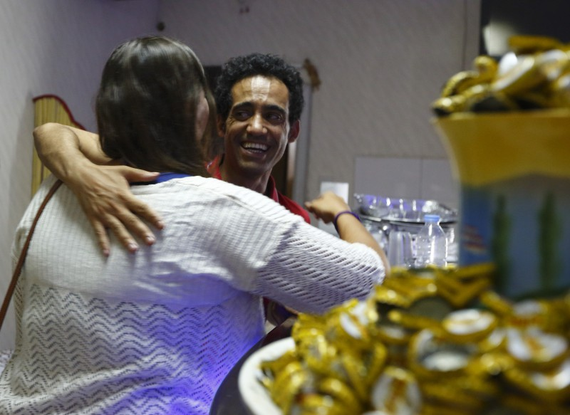 Eritrean restaurateur and entrepreneur Yonas Oukubamichael embraces a Maltese friend and client after serving dinner at his restaurant Selam in Hamrun June 22, 2014.