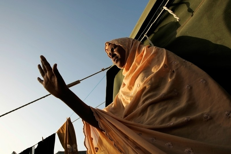 A Somali woman waves to a friend as she comes out of the tent they share at Hal Far Tent Village open centre for migrants at Hal Far outside Valletta, June 6, 2007. Many asylum seekers who are granted protection are released from detention into one of the open centres. Some opt to move to the community right away