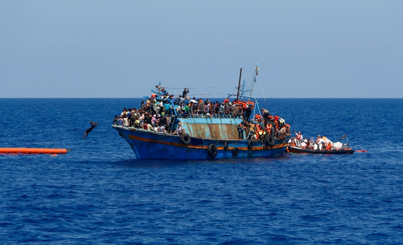 A migrant dives into the water from an overloaded wooden boat during a rescue operation off the coast of Libya