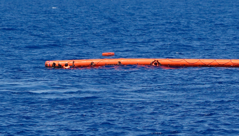 Migrants hang onto a flotation device during a rescue operation off the coast of Libya