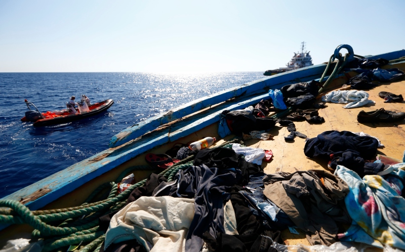 Migrants' belongings litter the deck of a wooden boat from which migrants were rescued 10.5 miles (16 kilometres) off the coast of Libya