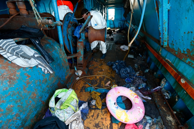 Migrants' belongings, including a child's buoyancy ring, litter the deck of a wooden boat from which migrants were rescued 10.5 miles (16 kilometres) off the coast of Libya