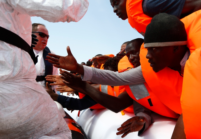 Migrants reach out to grab hold of Migrant Offshore Aid Station  rescuers on a RHIB before  being taken to the MOAS ship MV Phoenix some 20 miles off the coast of Libya