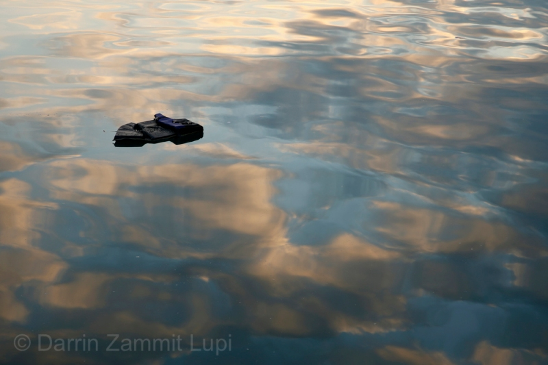 A lifejacket floats on the surface of the water at the port of Mytilene on the Greek island of Lesbos